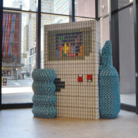 Canstruction build created with canned goods depicting hand holding a Nintendo Gameboy playing Tetris thumbnail